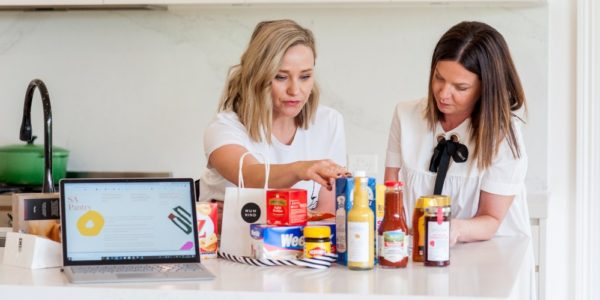 two women with packaged good for charity